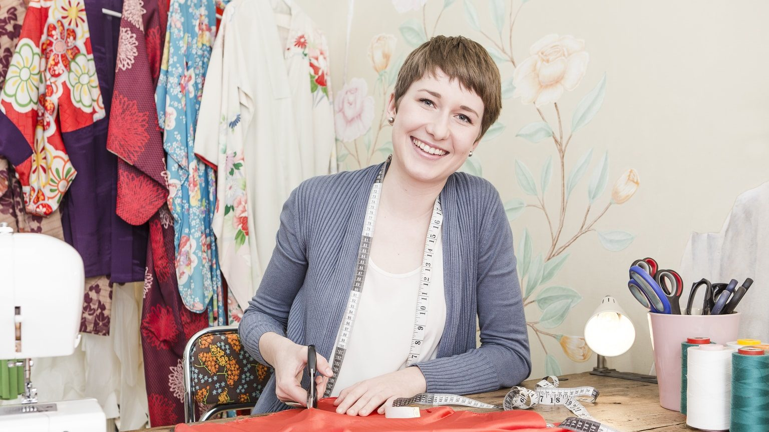 Smiling young woman sewing and doing crafts