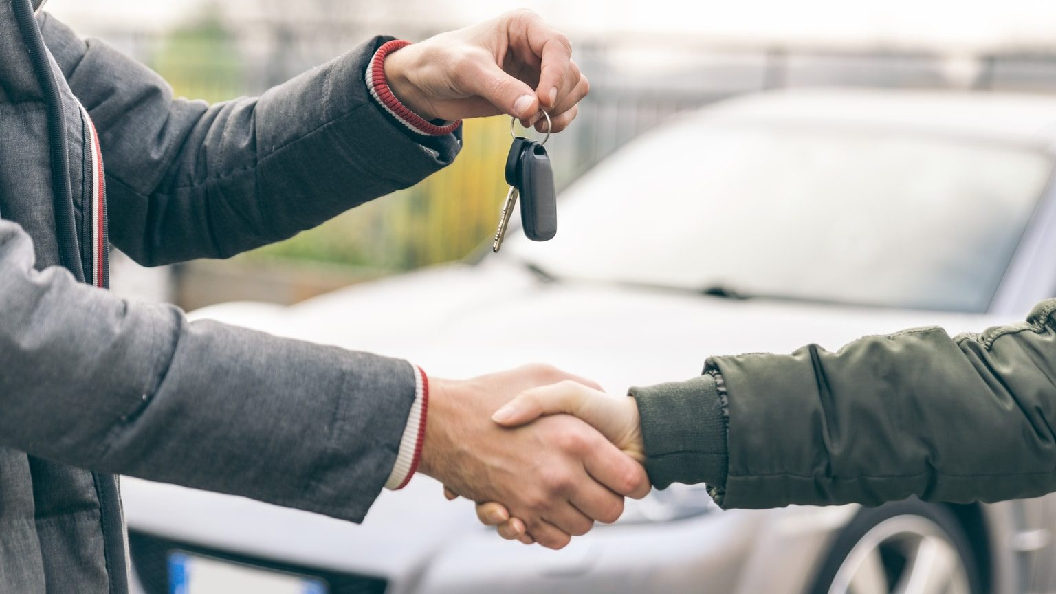 Car salesman handing new vehicle owner keys to a car