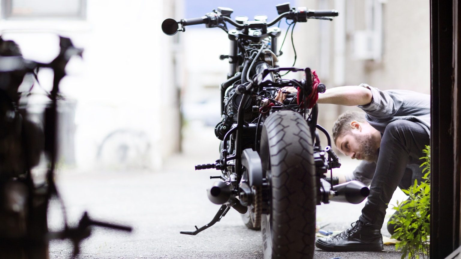 Man Fixing Motorcycle In Garage
