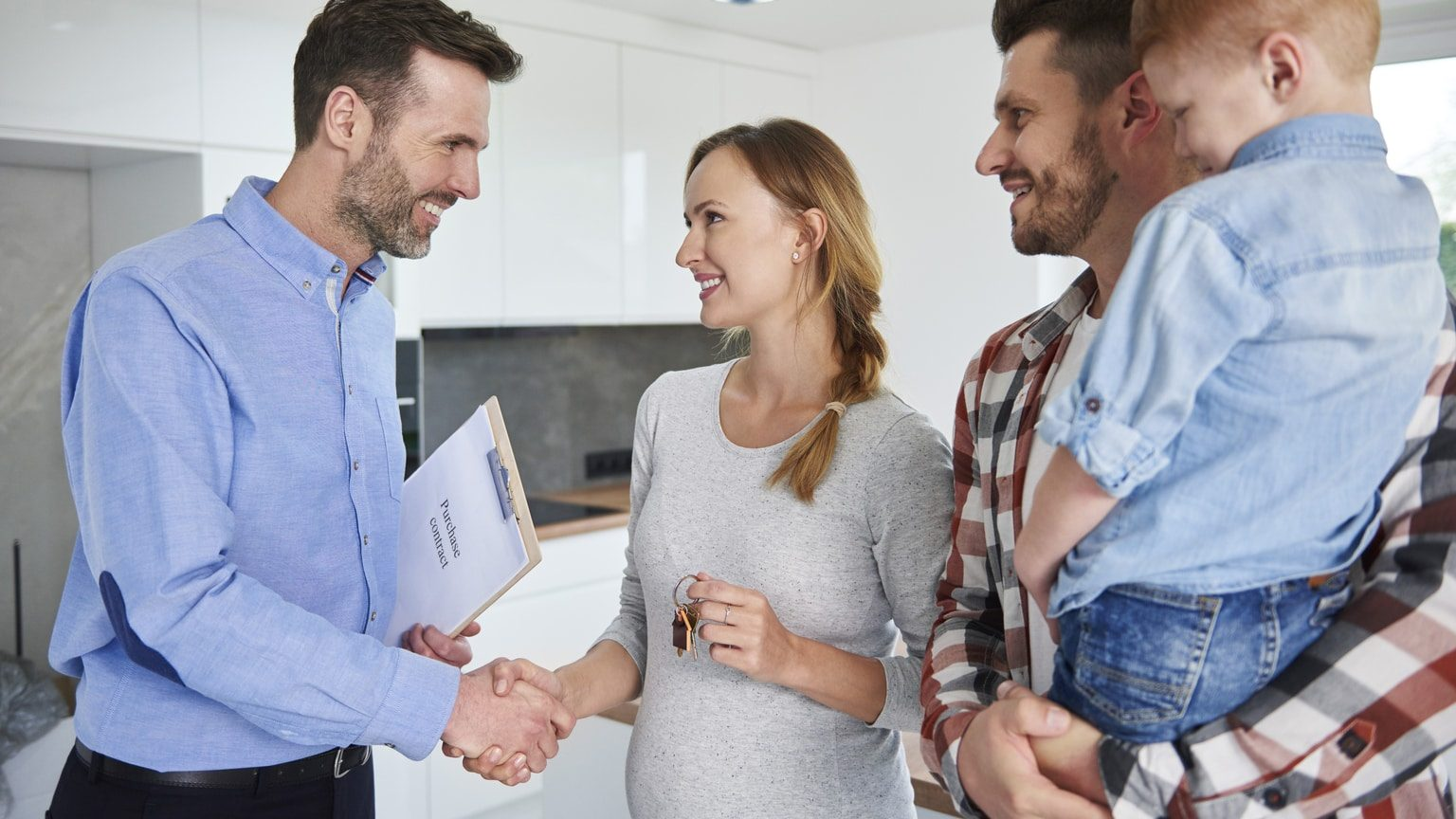 Young family accepting keys to a home