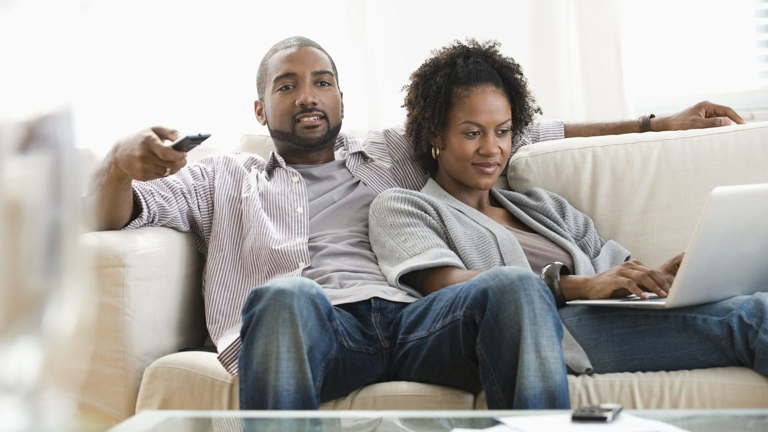 Couple on a couch with a laptop watching tv