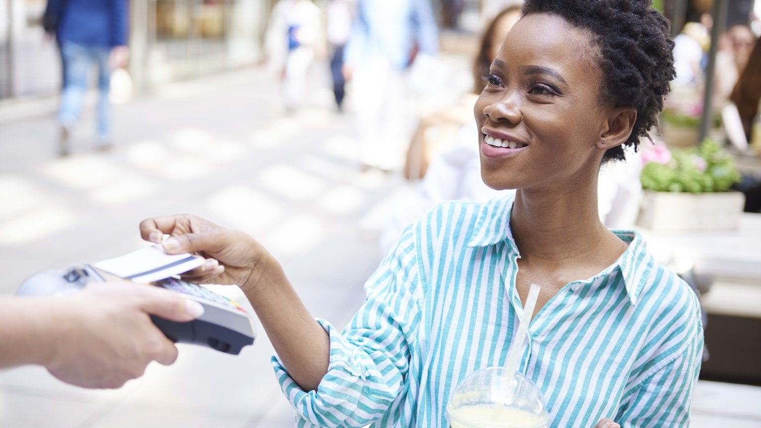 Young woman paying for her drink with a credit card