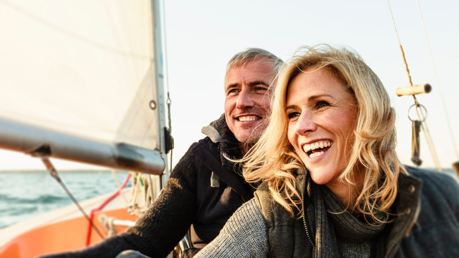 An older couple smiling on a sailing boat