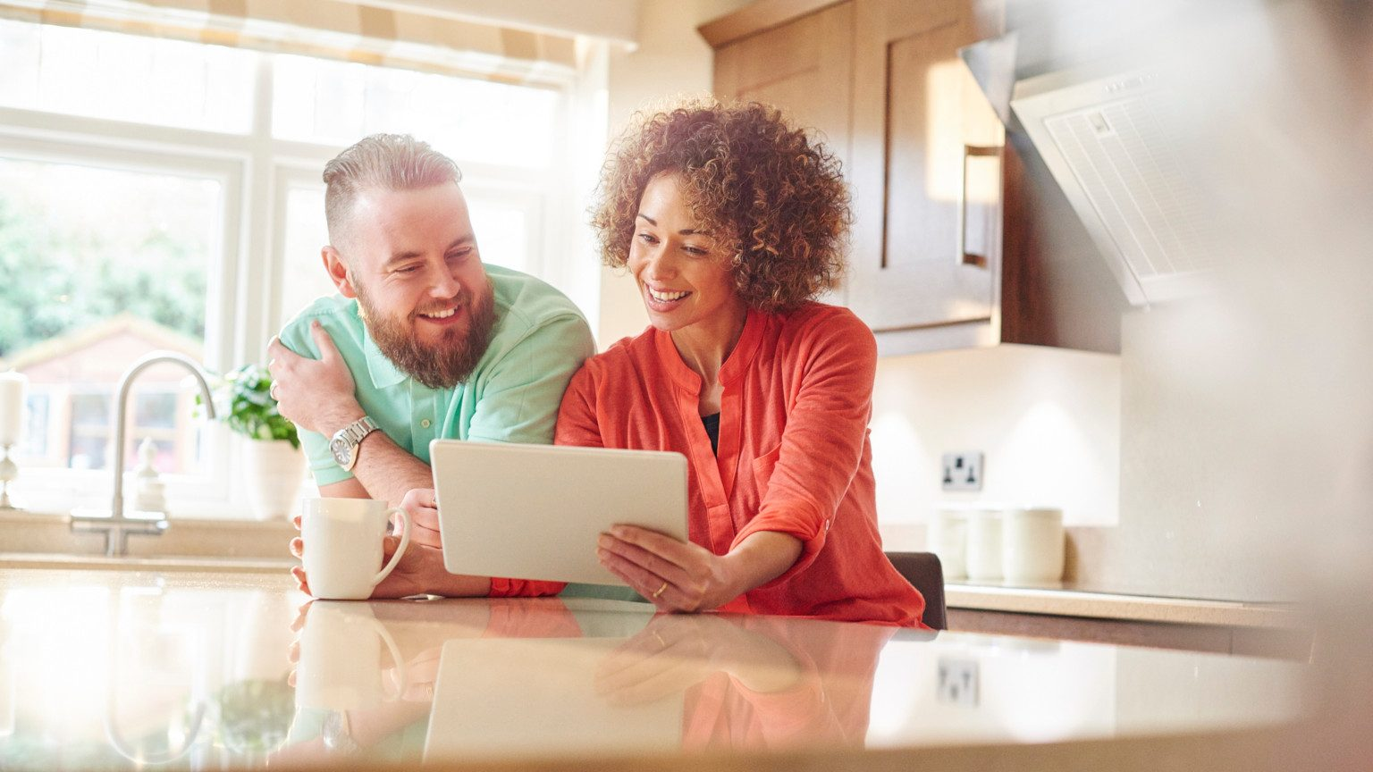 Smiling couple in their kitchen looking at a tablet