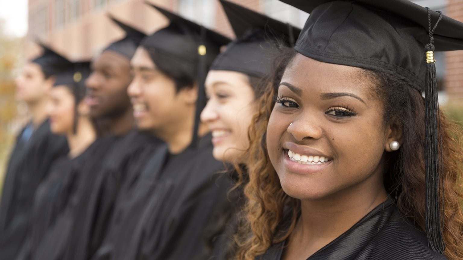 Smiling woman in row of graduates, high school, college, university