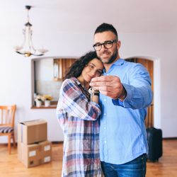 Couple holding key and moving into new house