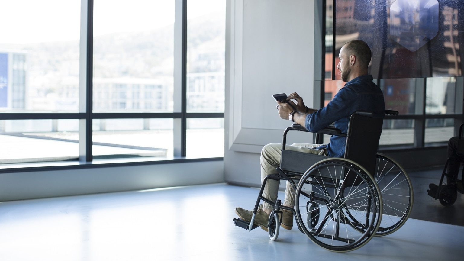 Man in wheelchair using tablet