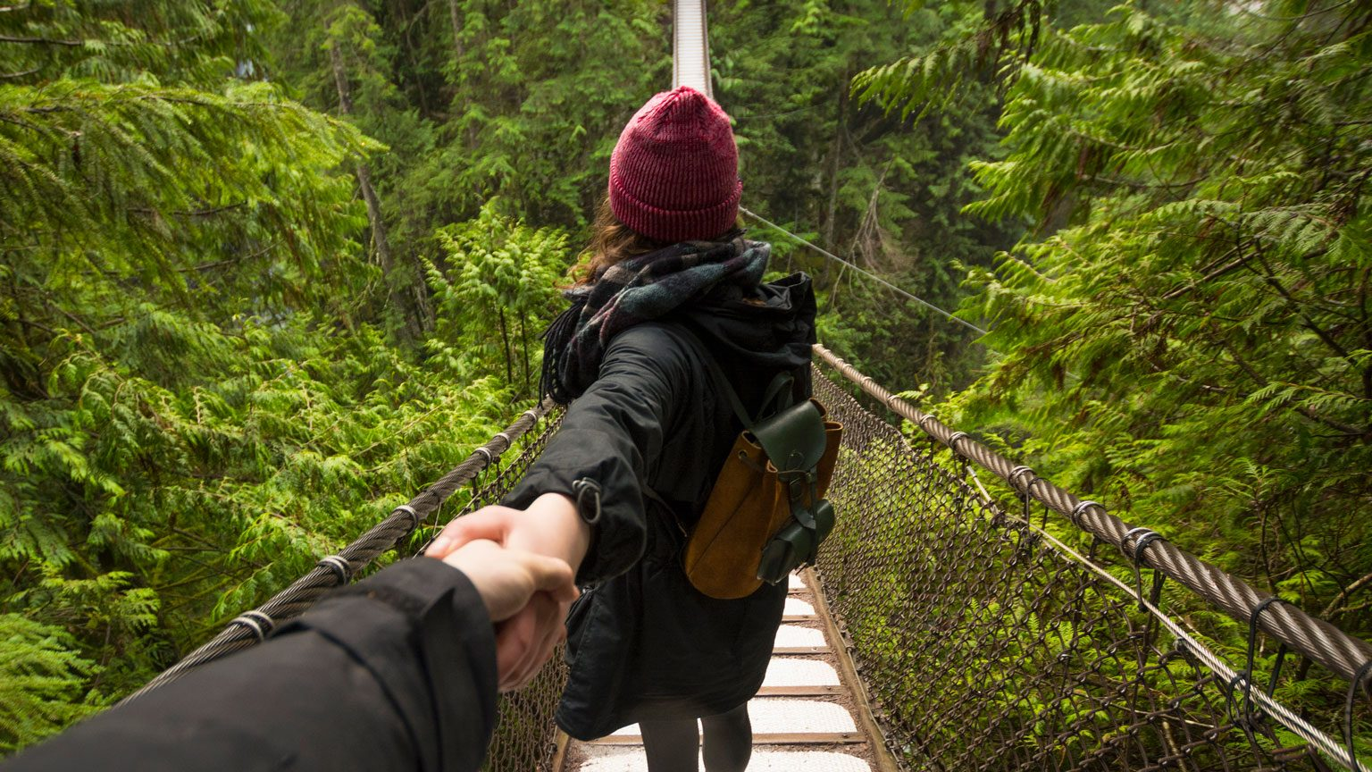 Woman on Lynn canyon suspension bridge holding mans hand, North Vancouver