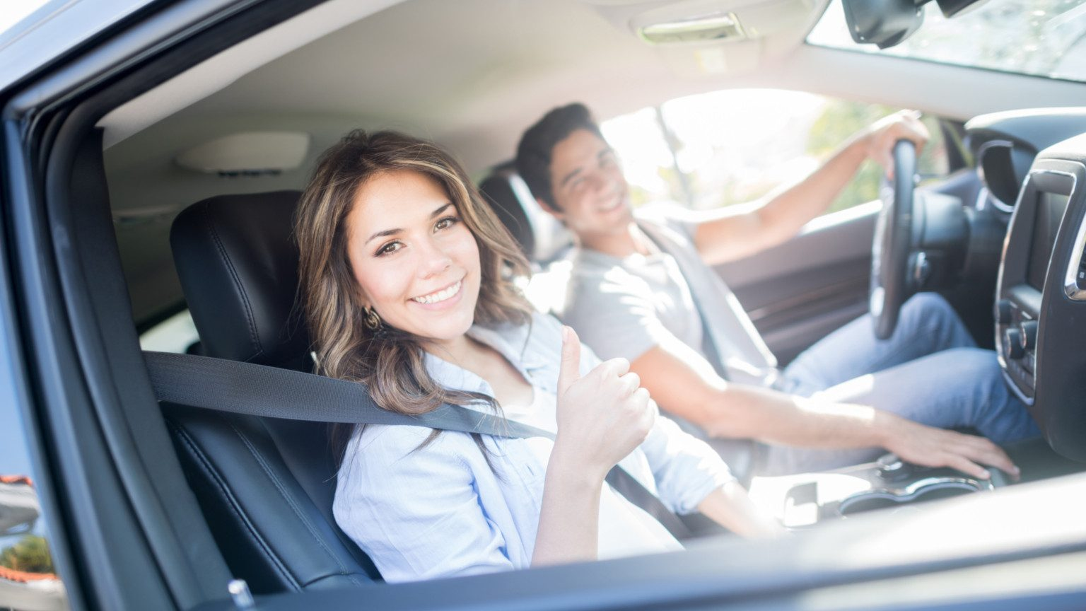 Woman giving thumbs up from passenger seat inside car