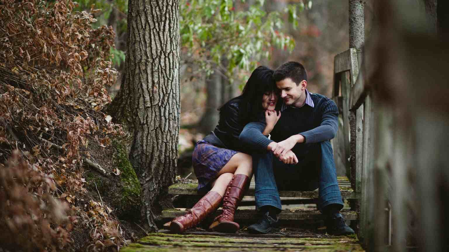 A couple sits on an old pathway and embraces on a cool autumn afternoon