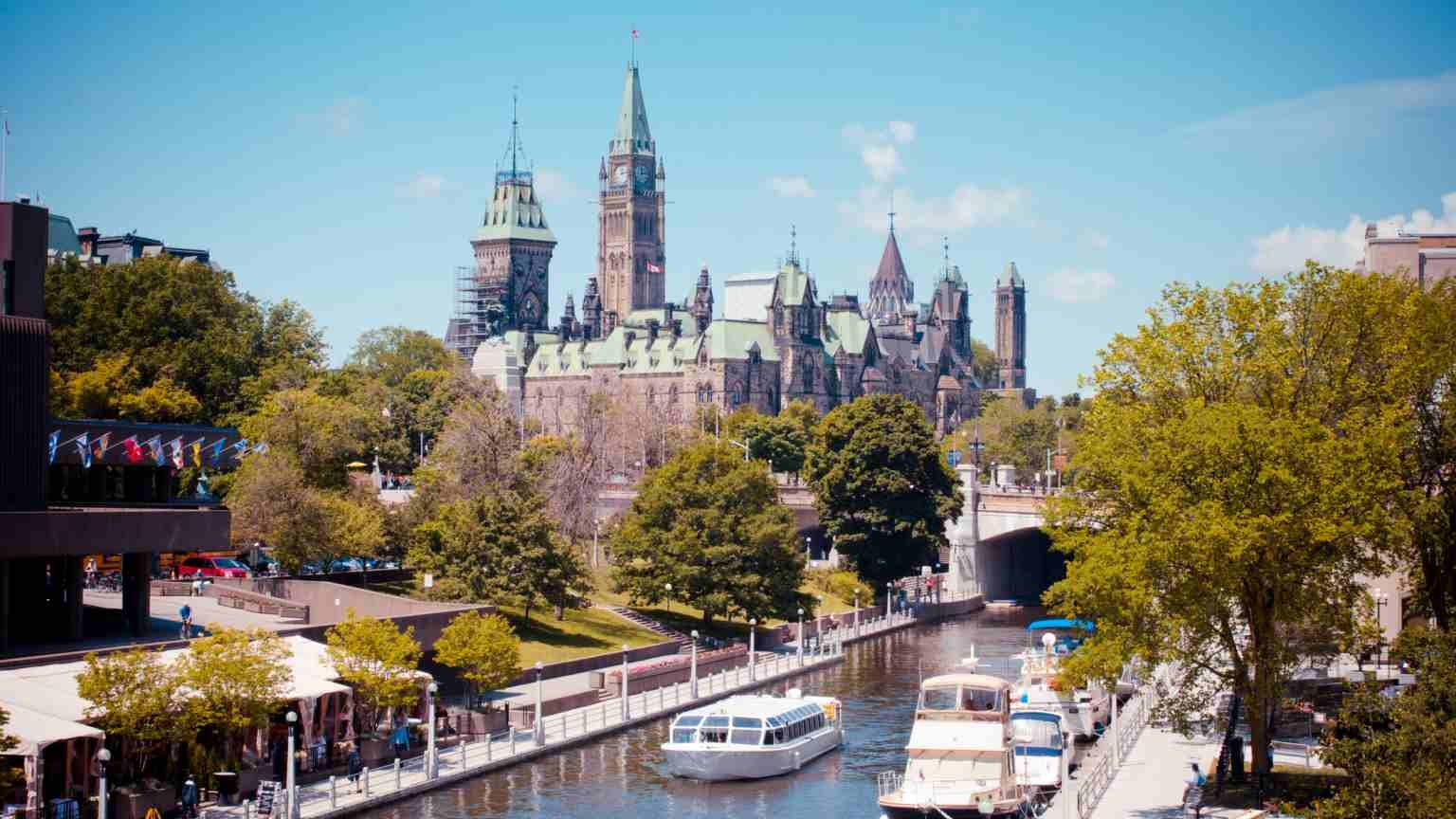 Summer day on Ottawa's historic Rideau Canal, with Canada's Parliament Buildings and Peace Tower looming in background and National Arts Centre to left.