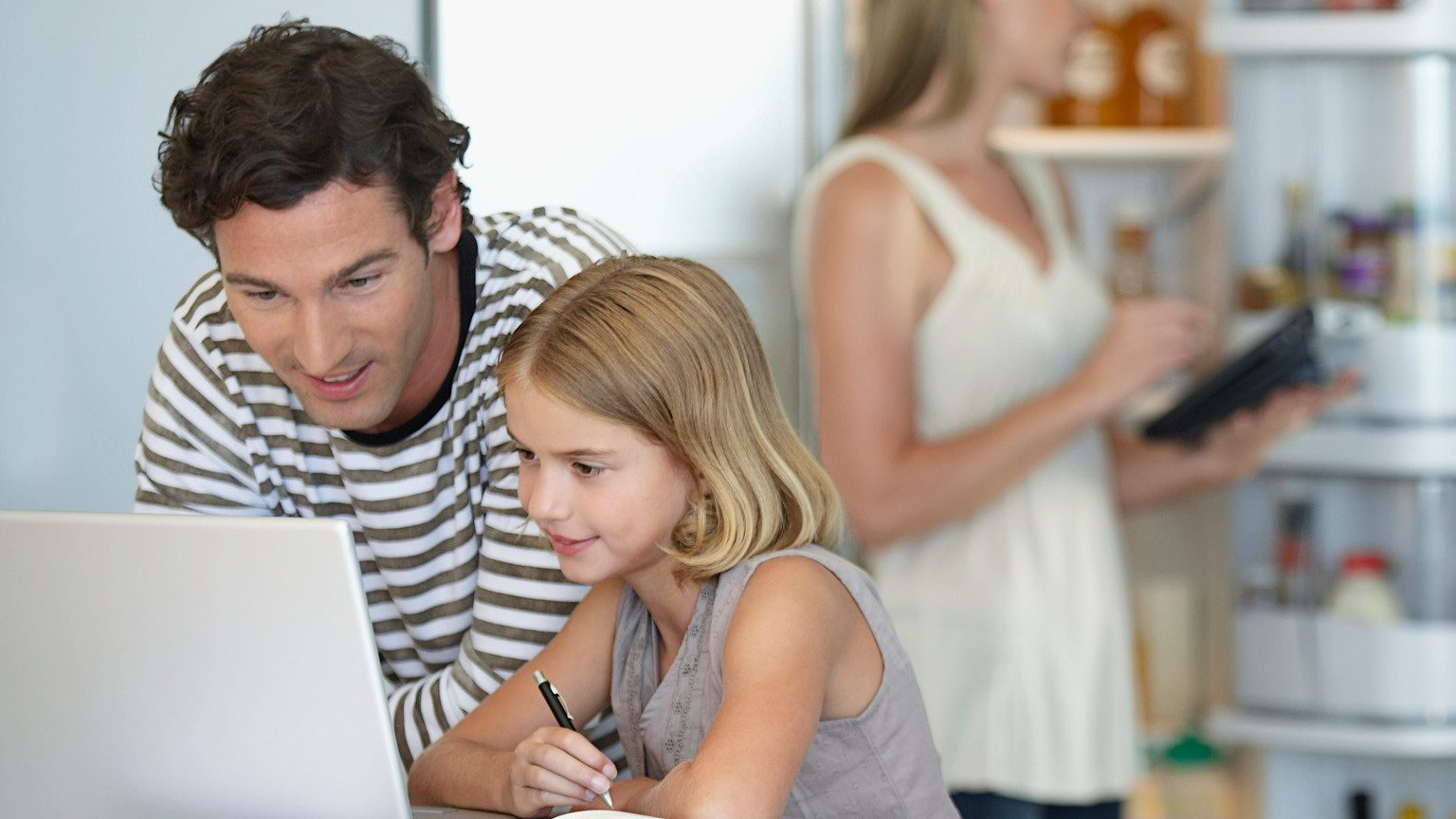 Young father and daughter looking at a laptop together