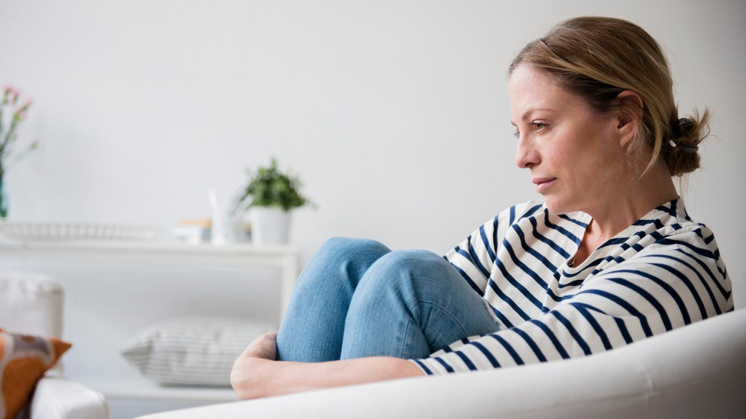 Women sitting holding her legs while staring off into the distance