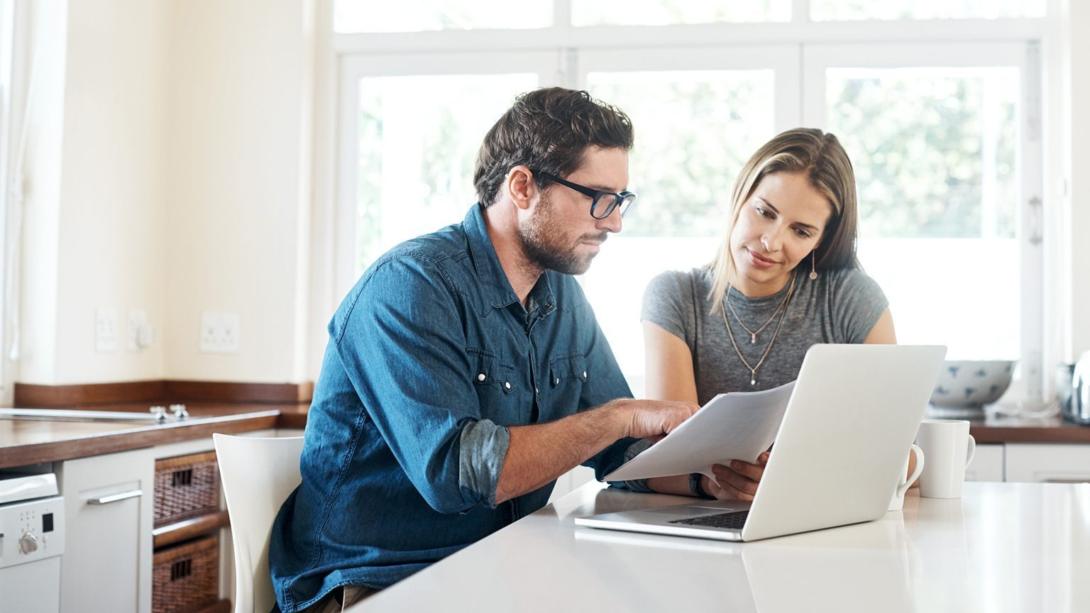 Couple looking over a paper and laptop