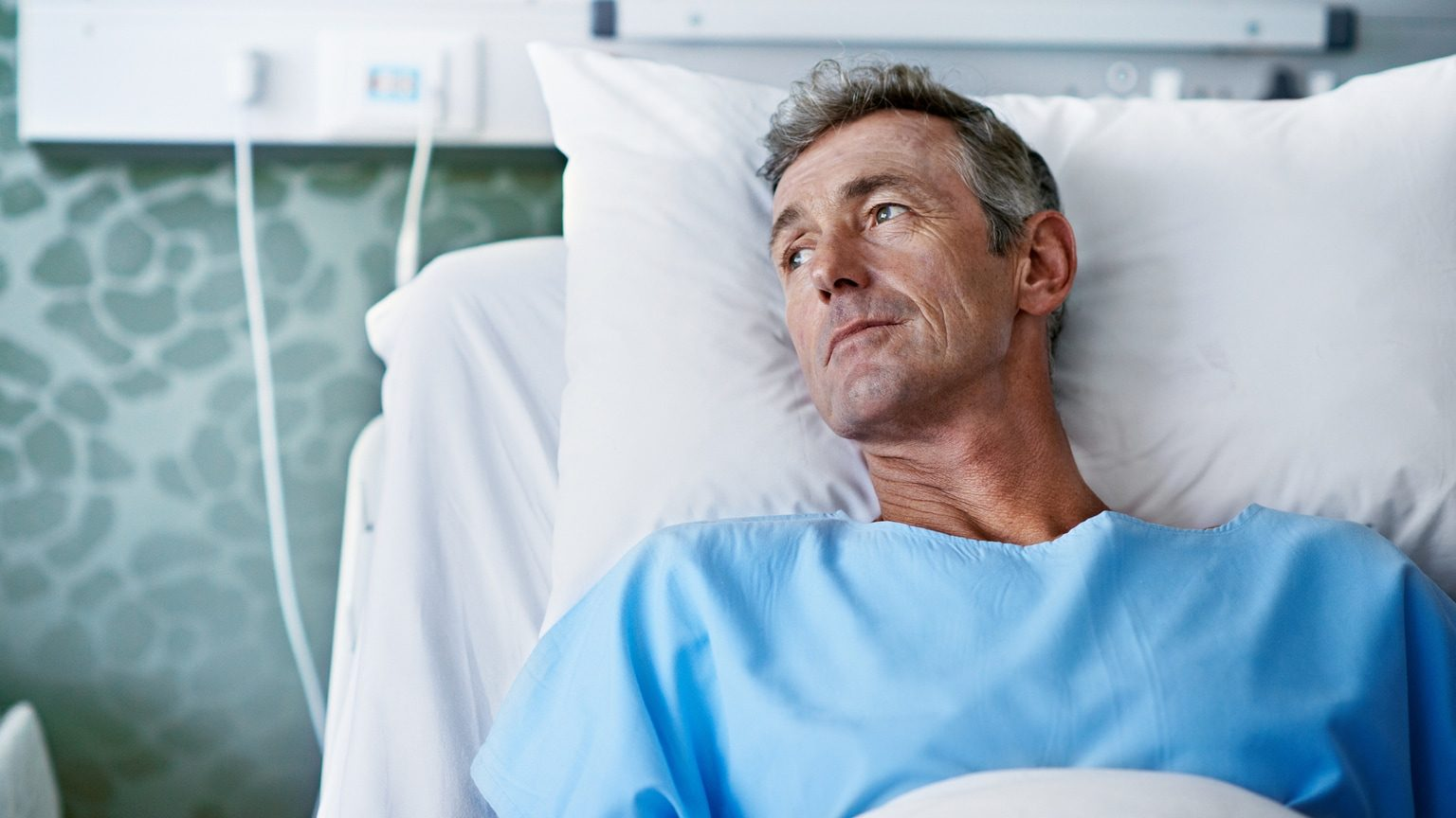 Sick man lying in a hospital bed