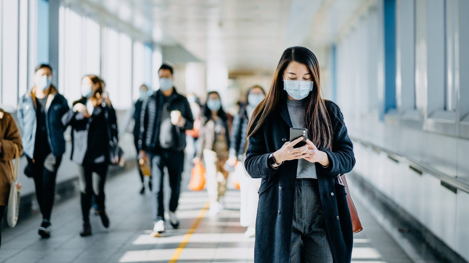 Woman walking through airport wearing a protective face mask