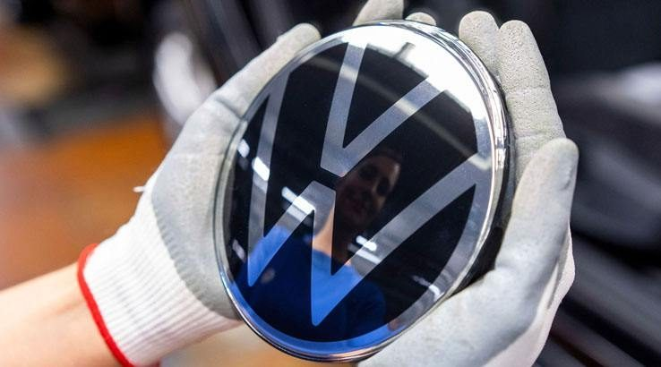 Gloved hands holding item with Volkswagen logo