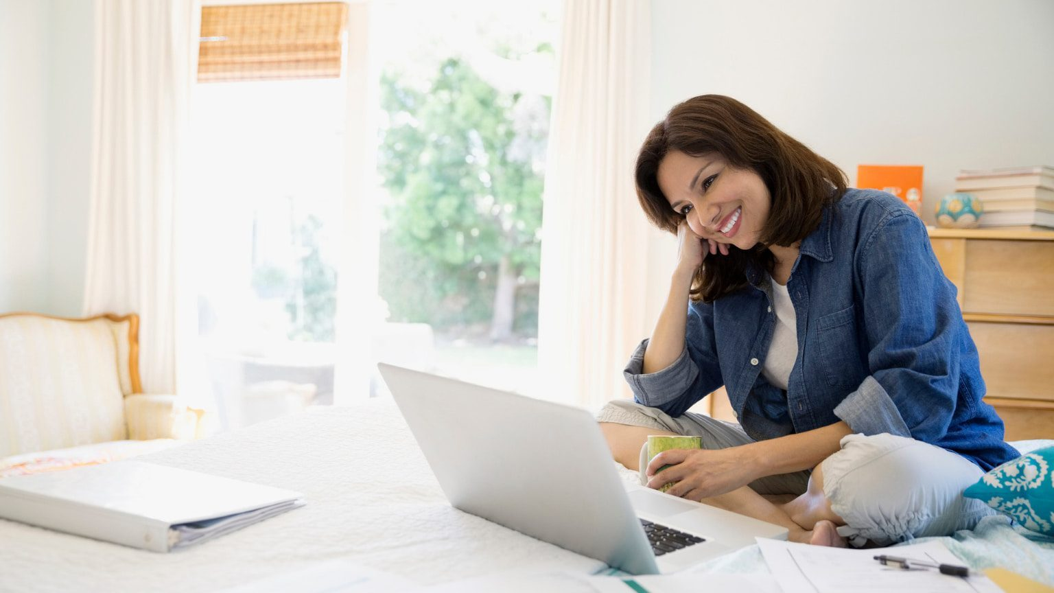 Seated, smiling brunette woman looking at her laptop