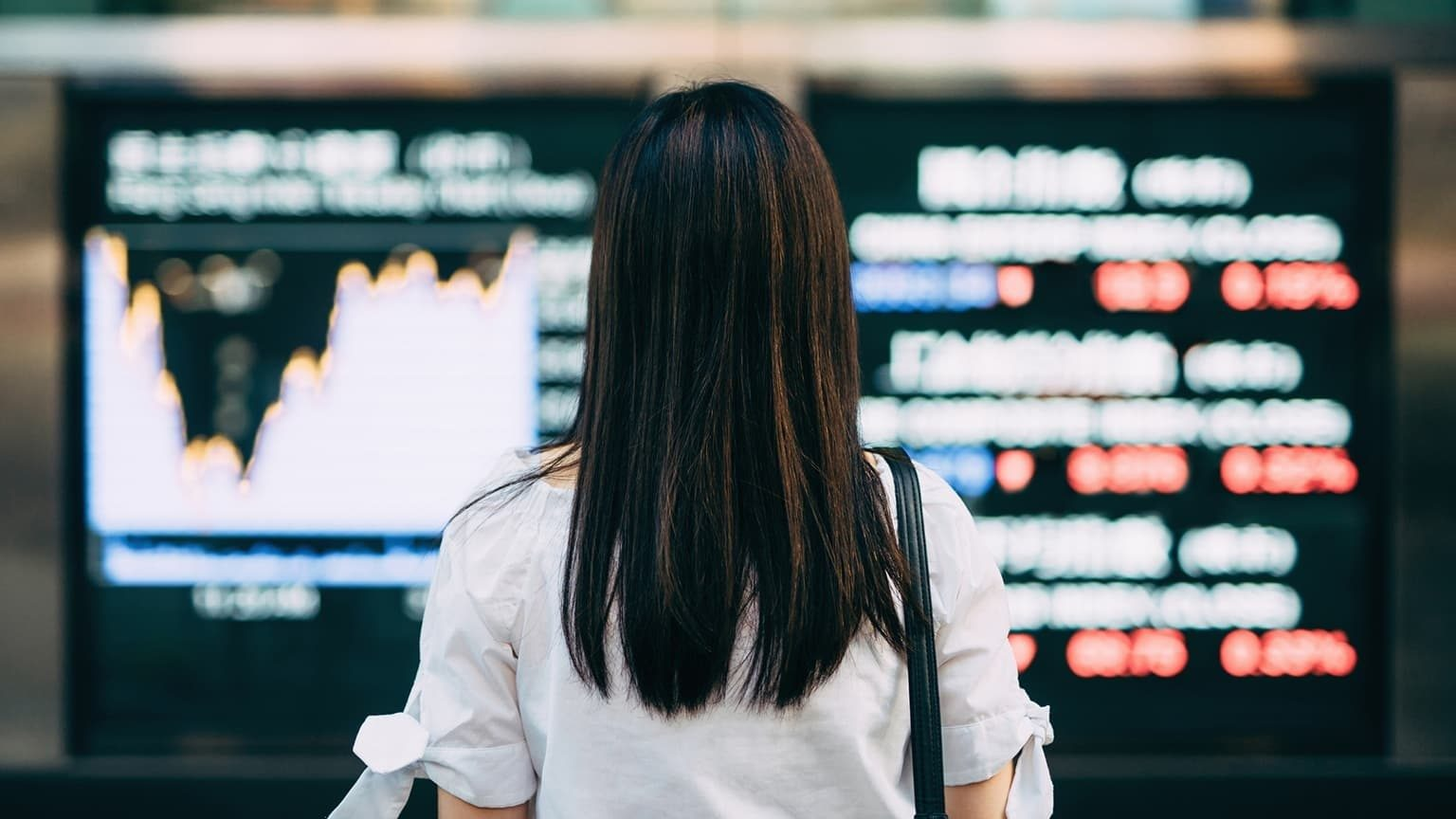Rear view of businesswoman looking at stock exchange market display screen