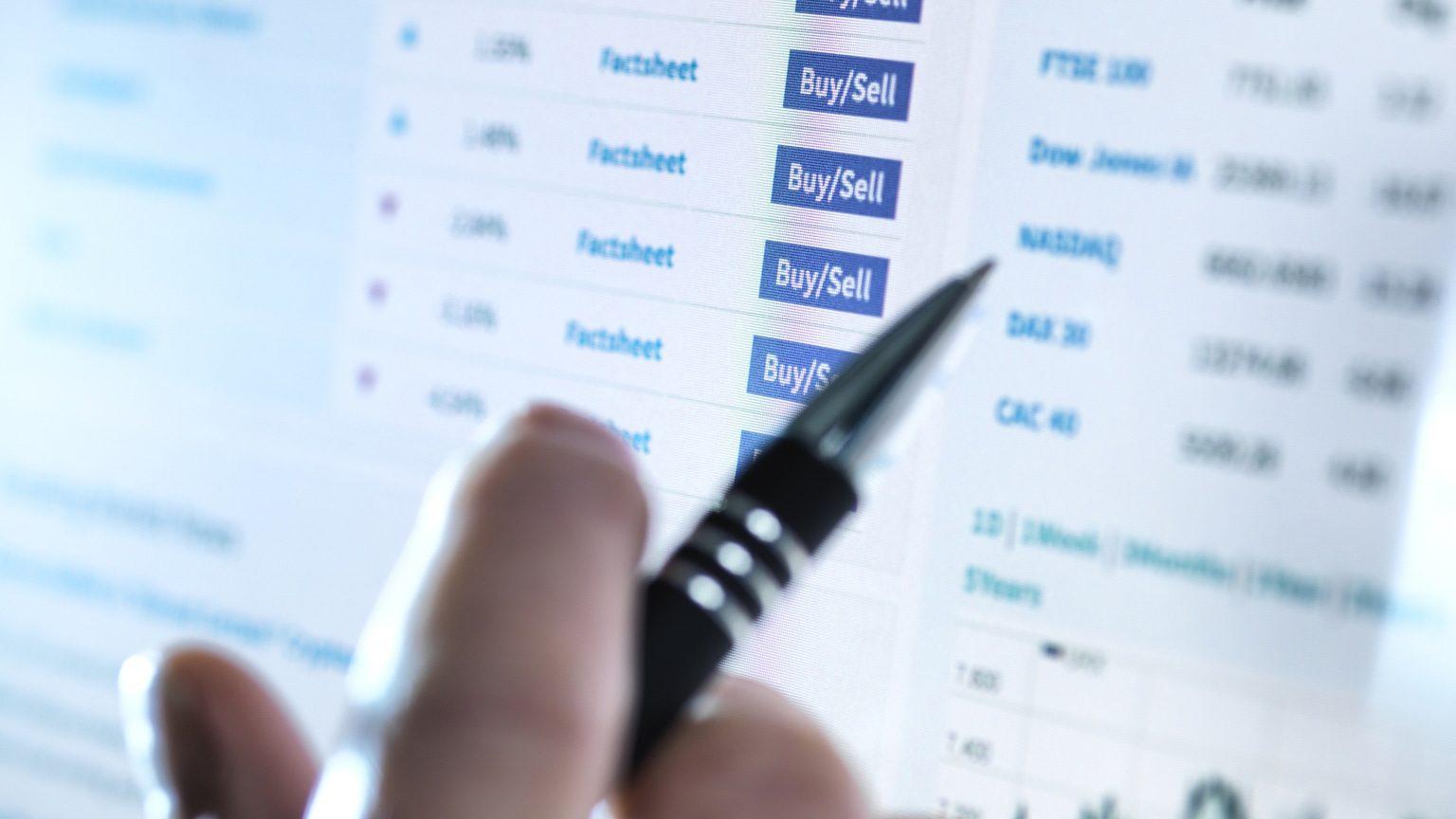 Closeup of hand running through list of stocks on computer