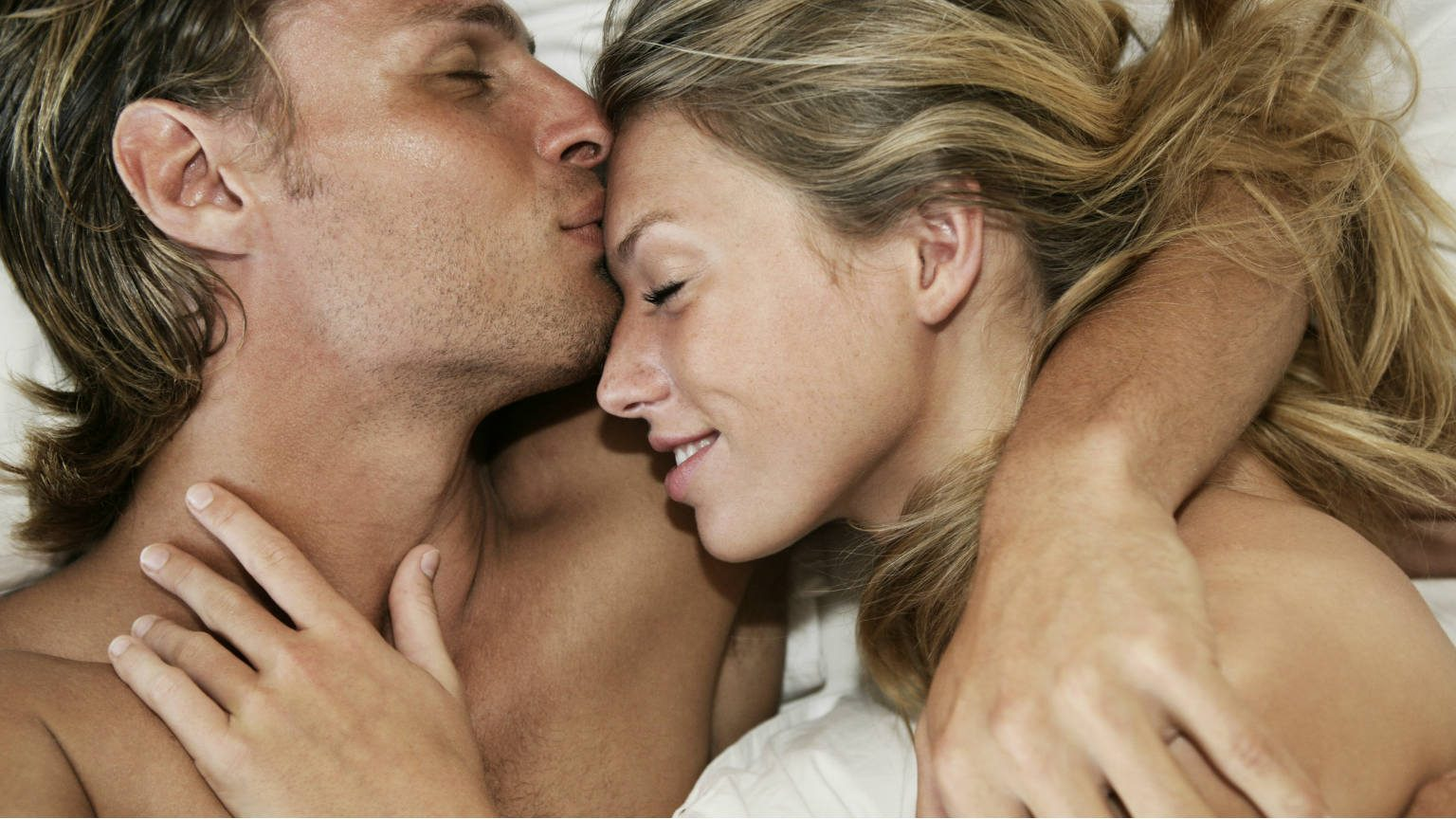 Men kissing woman on the forehead