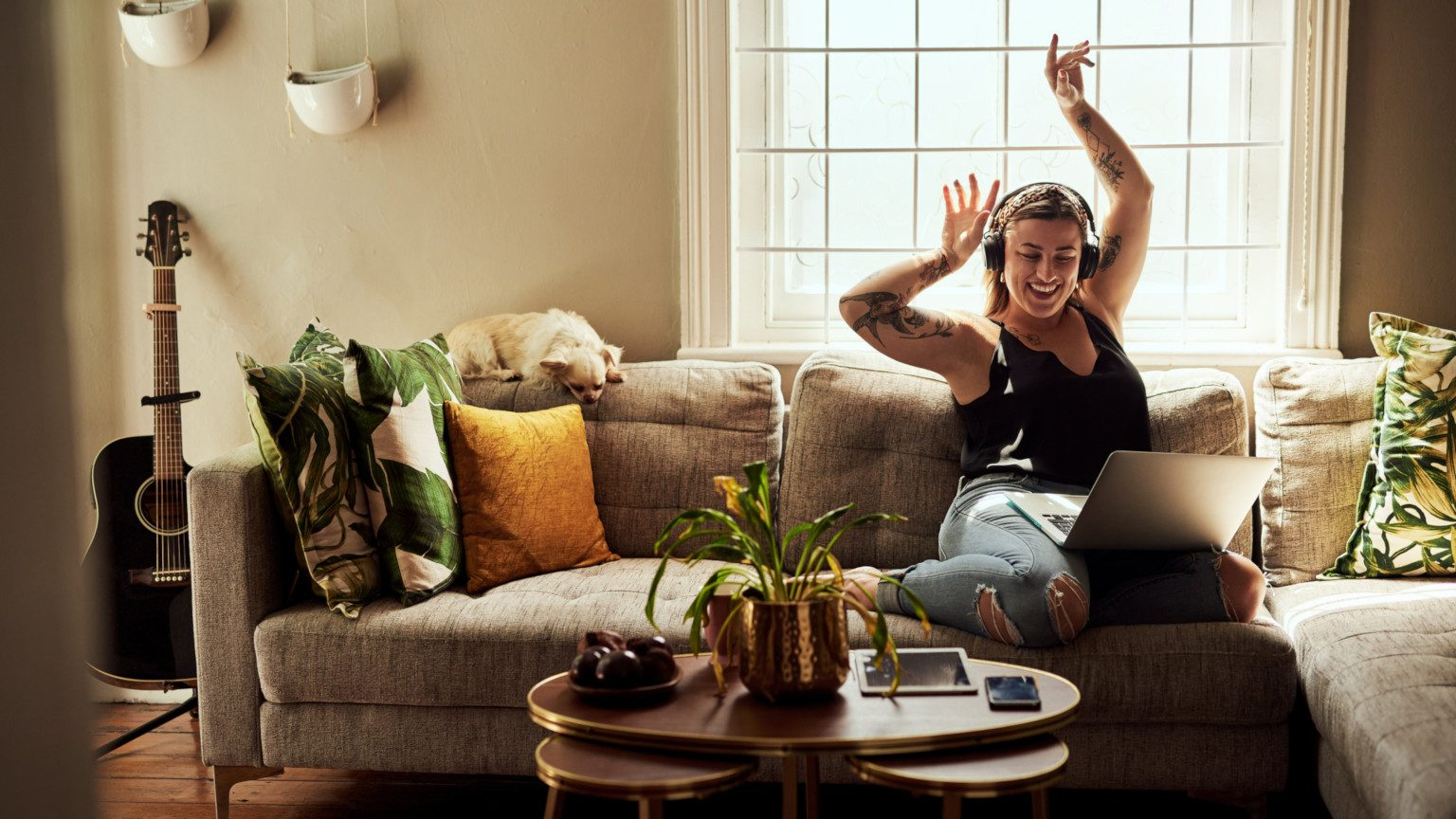 Woman sitting on her couch with laptop on headphones with her hands in the air