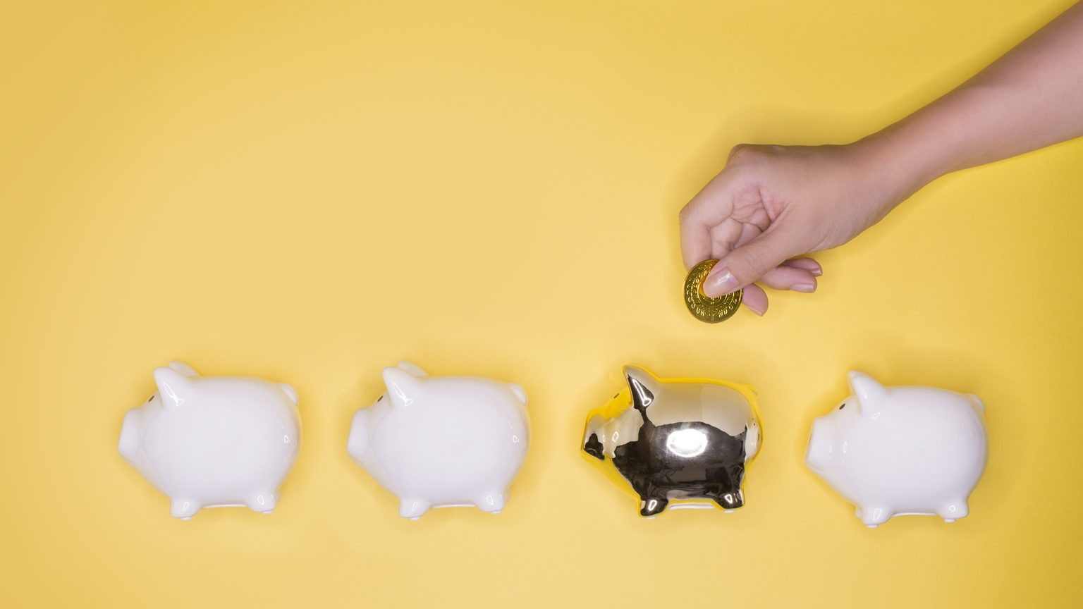 Hand putting coin into a golden piggy bank