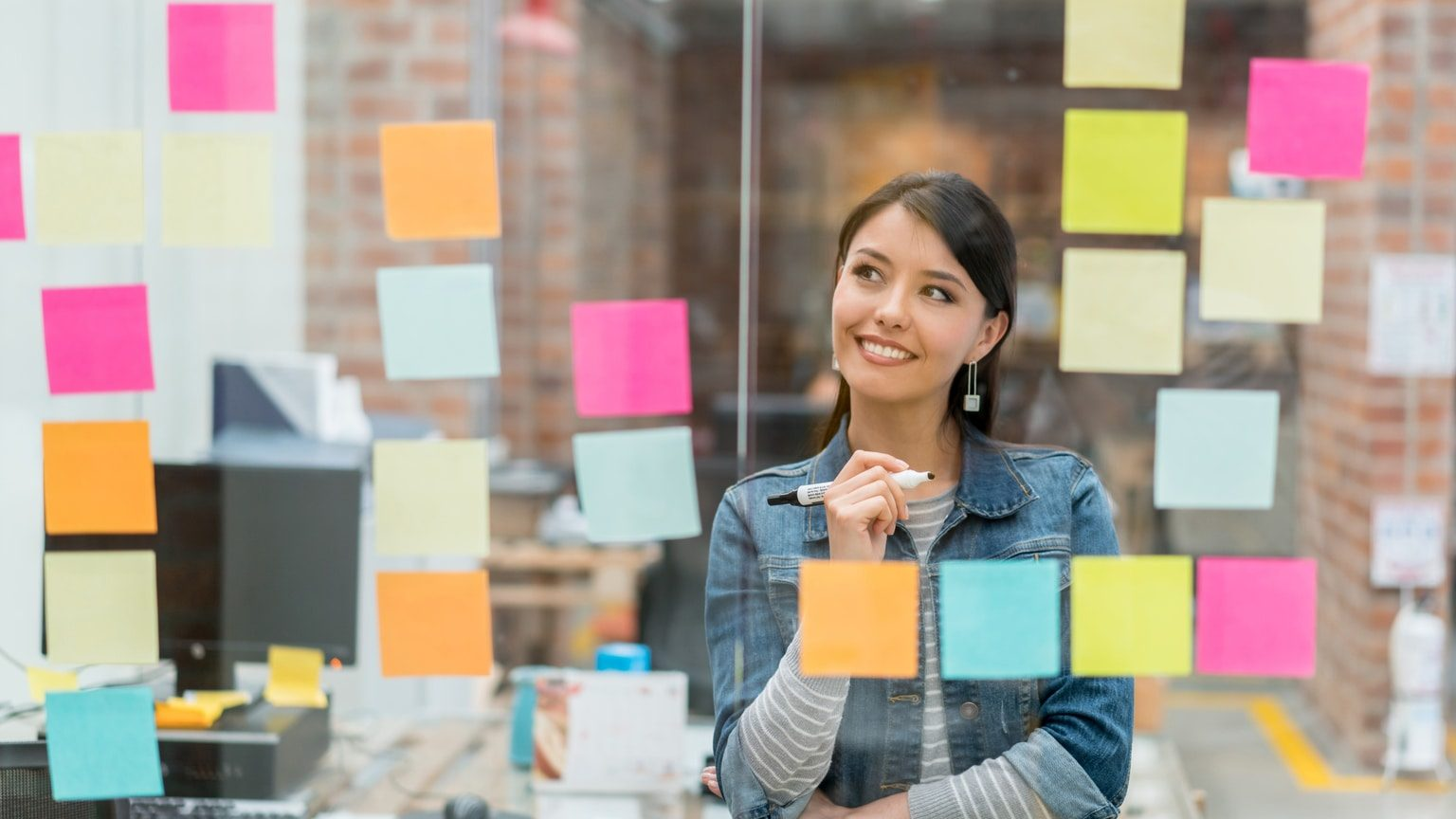 Smiling woman writing a marketing plan on sticky notes
