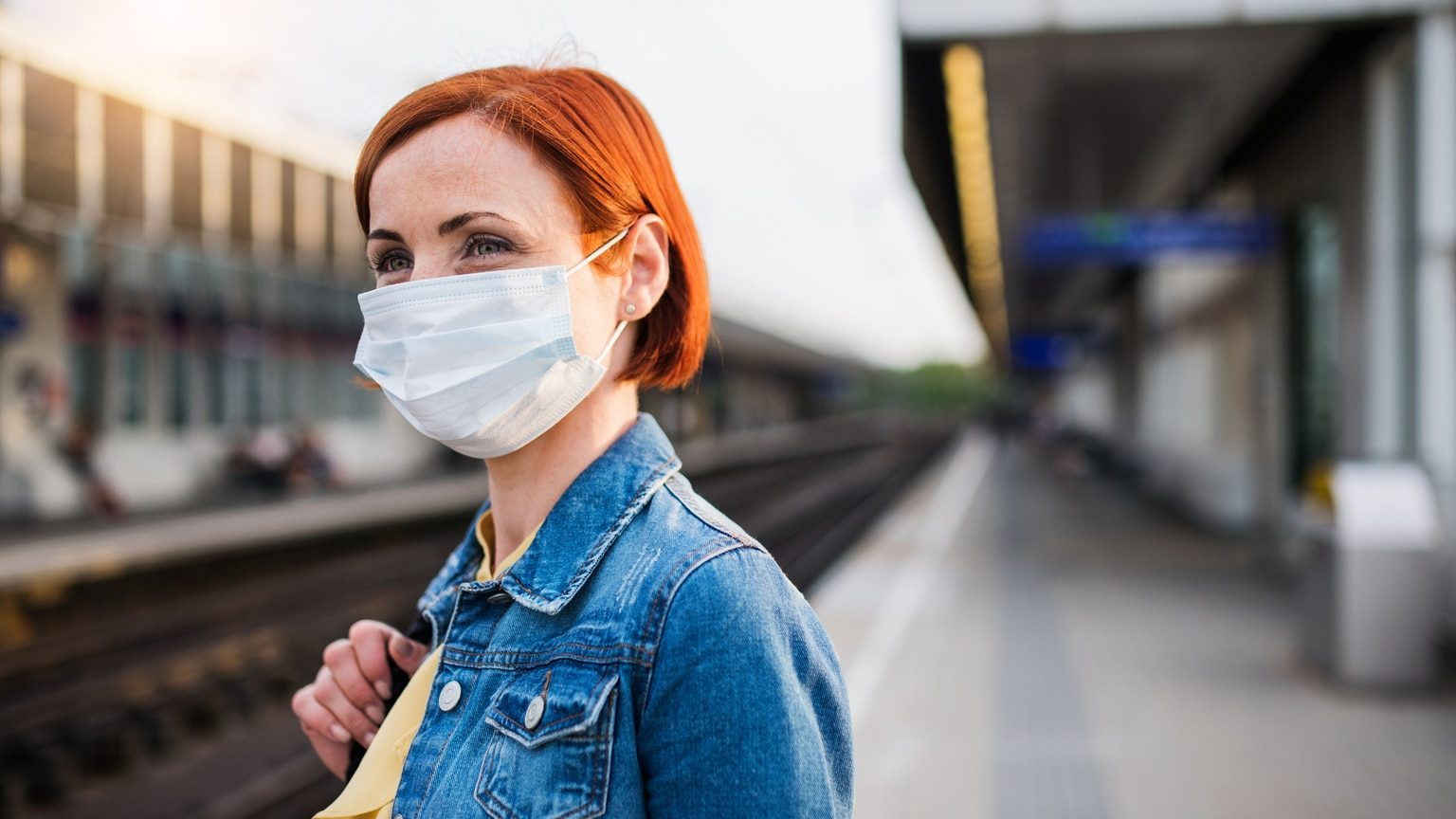 Woman at train station wearing protective face mask