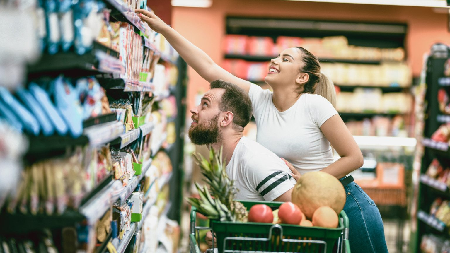 Girl piggy-backing on guy trying to reach food on a grocery store shelf