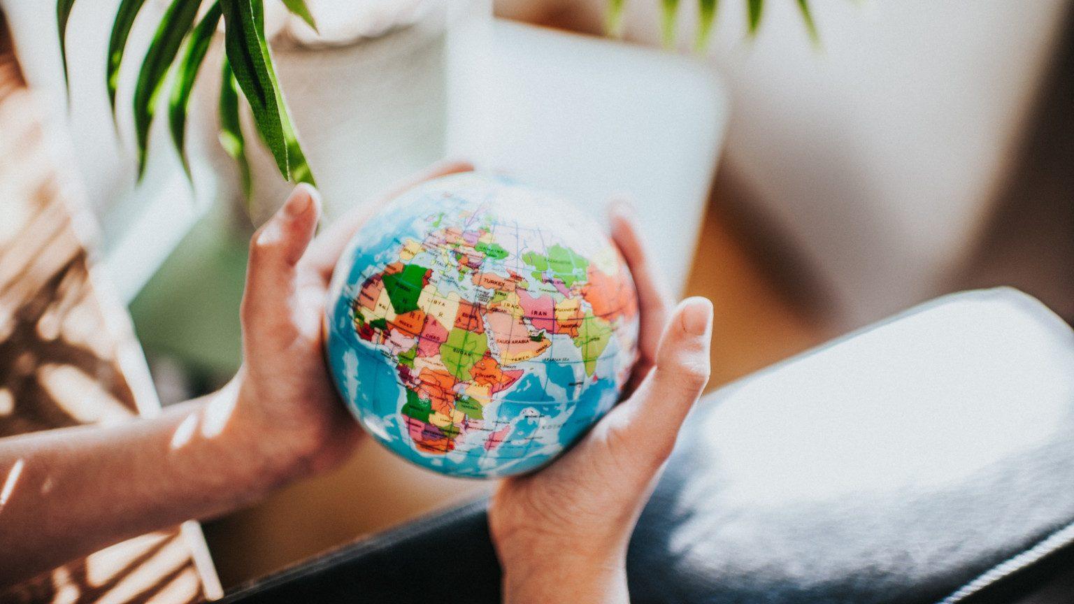 Hands holding a mini globe