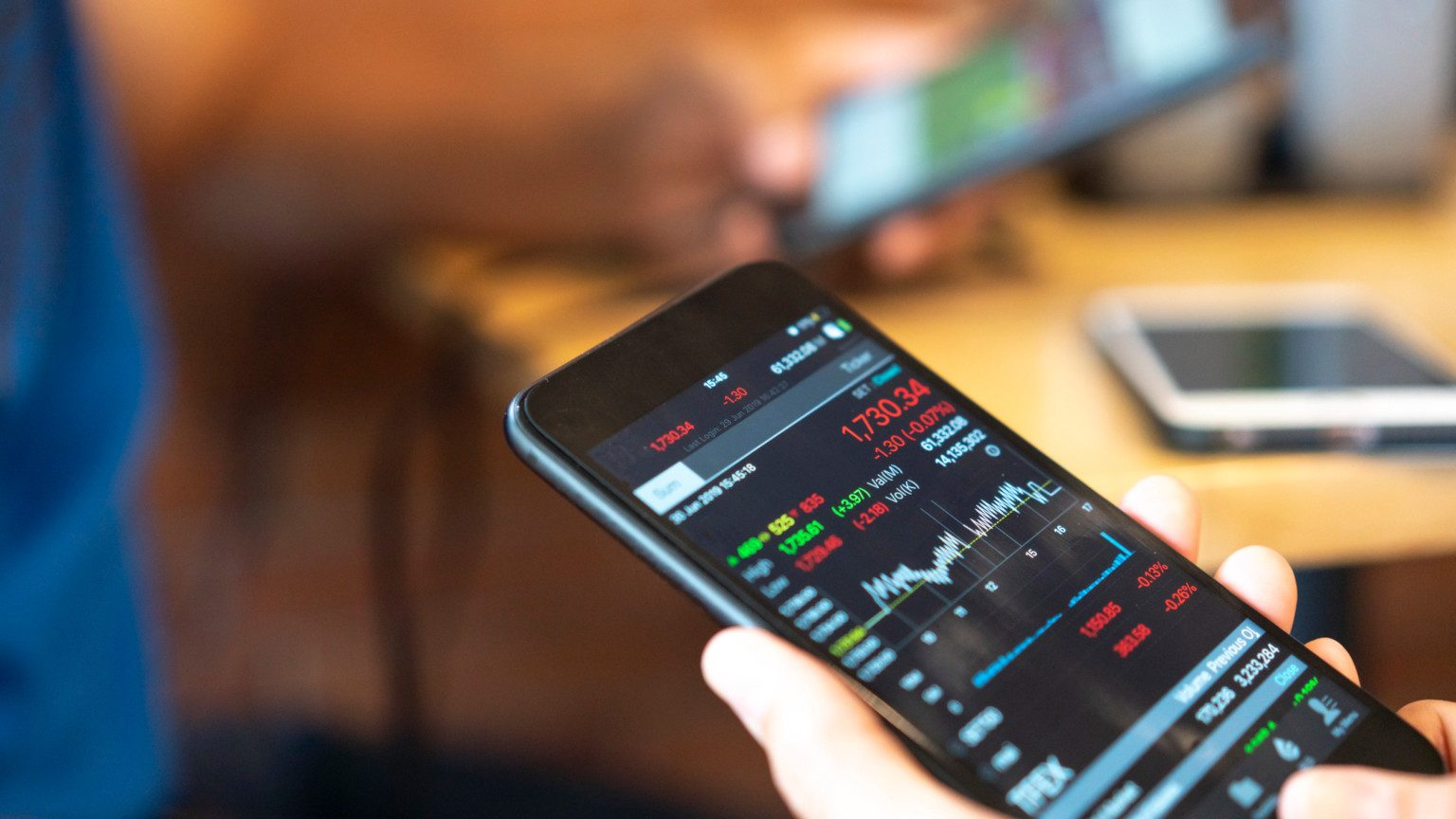 Hand holding a smart phone with stock trading on screen