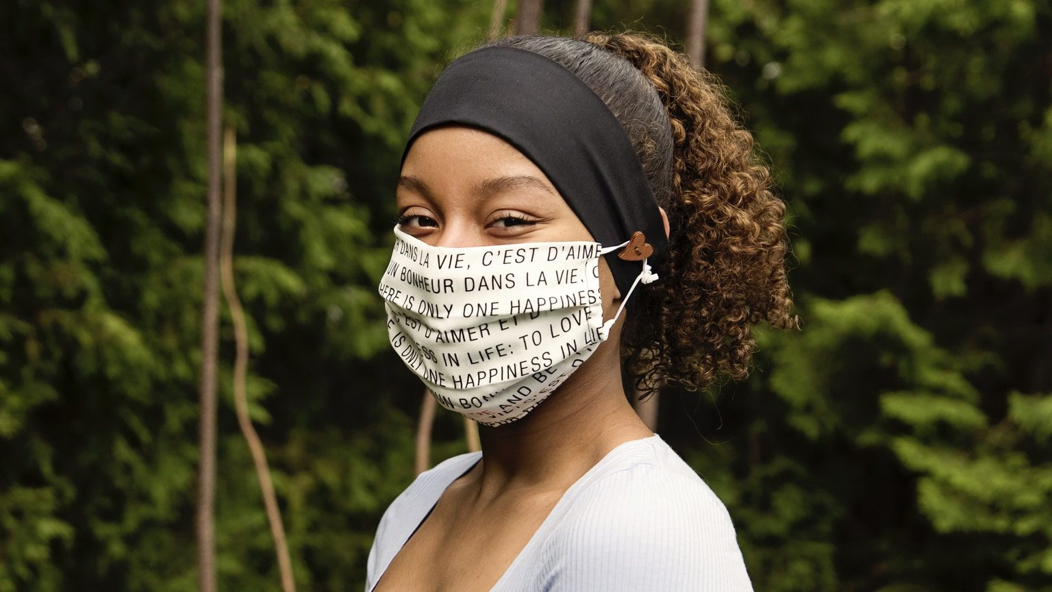 Young African woman wearing stylish protective face mask