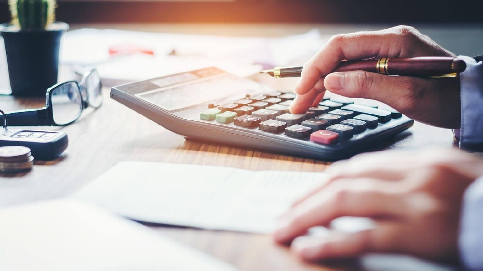 Closeup of a man using a calculator