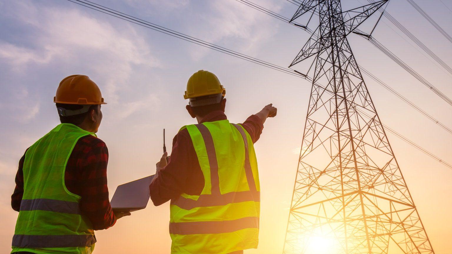 Utilities workers looking at electrical towers