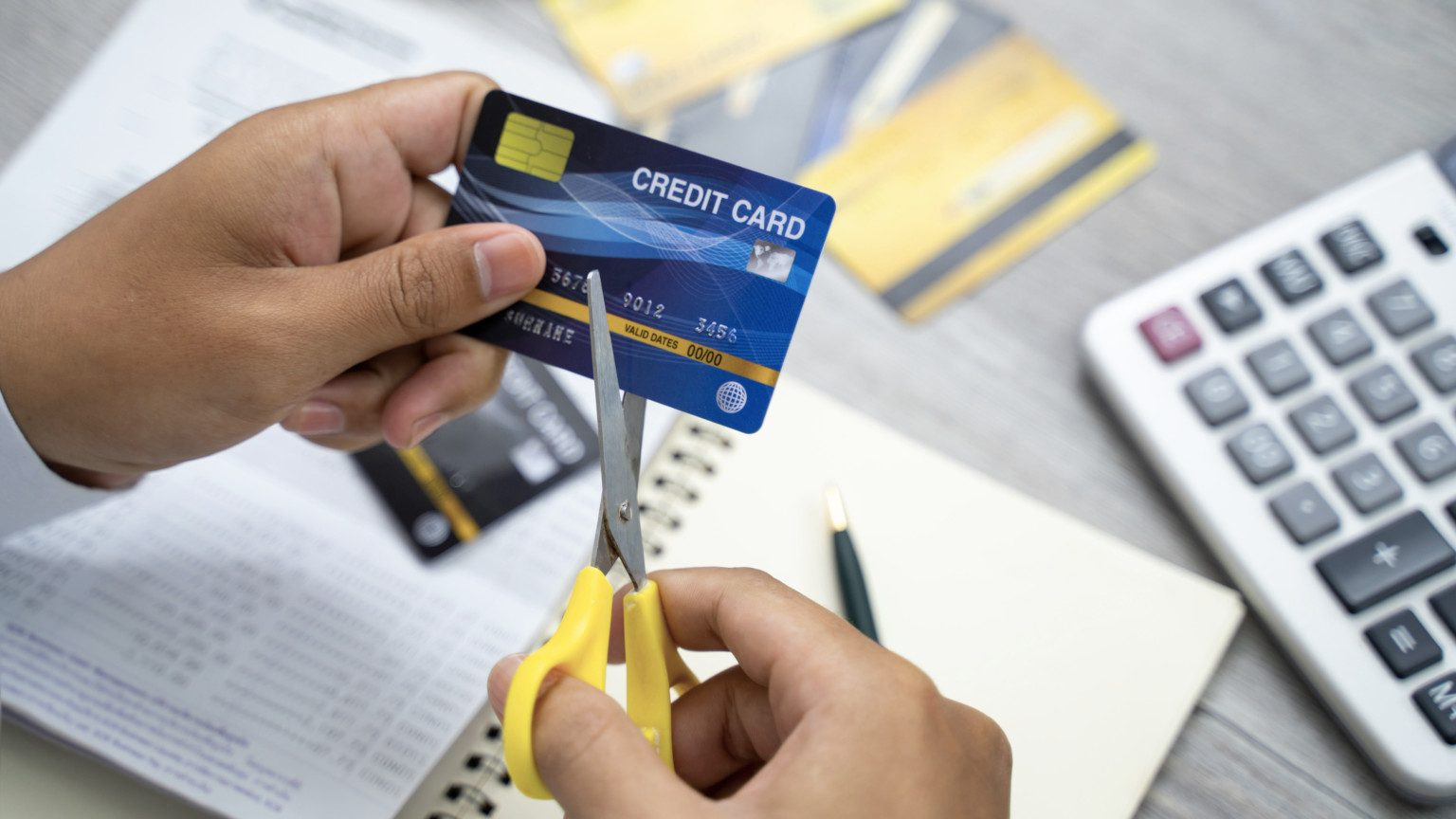 two hand cutting up a credit card