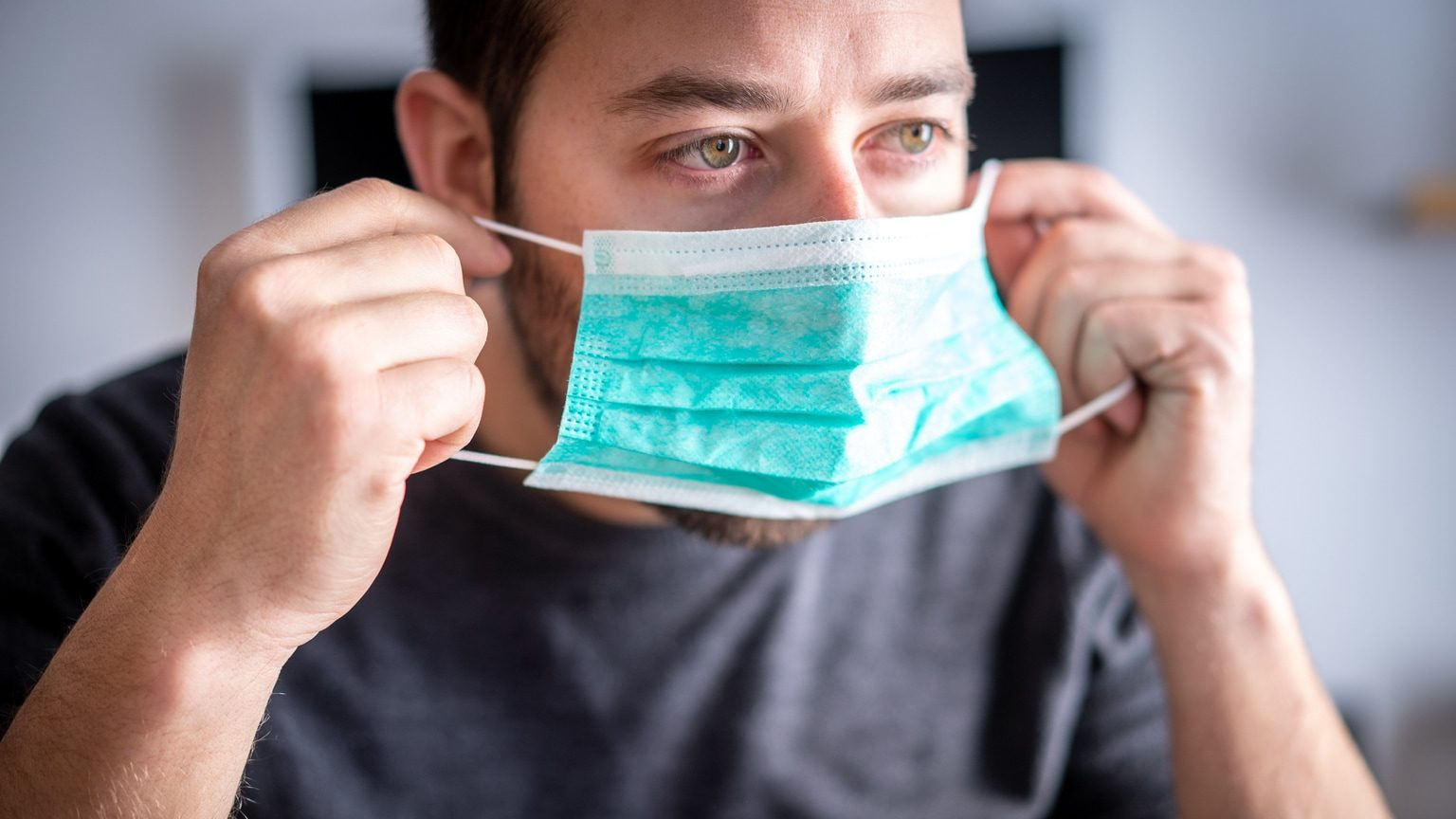 Bearded man putting on a disposable surgical mask