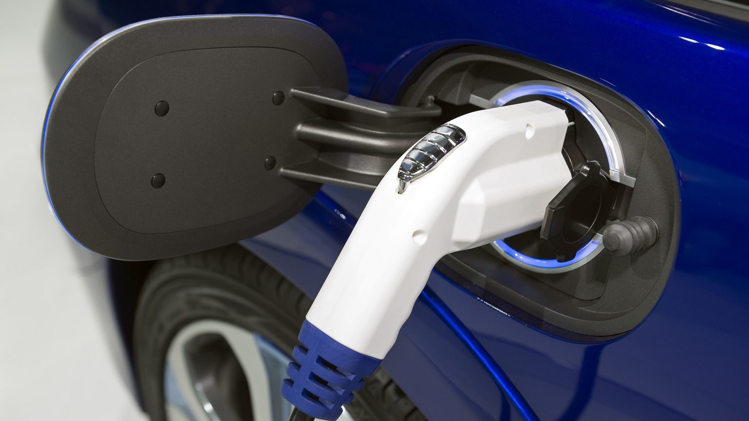 Closeup image of blue electric car being recharged