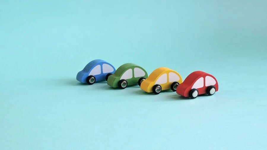 Colourful wooden toy cars on light blue-green background