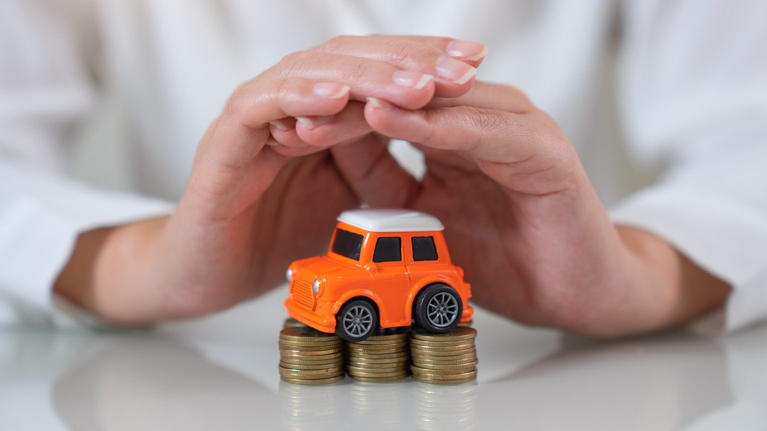 Hands Covering Toy Car And Coins