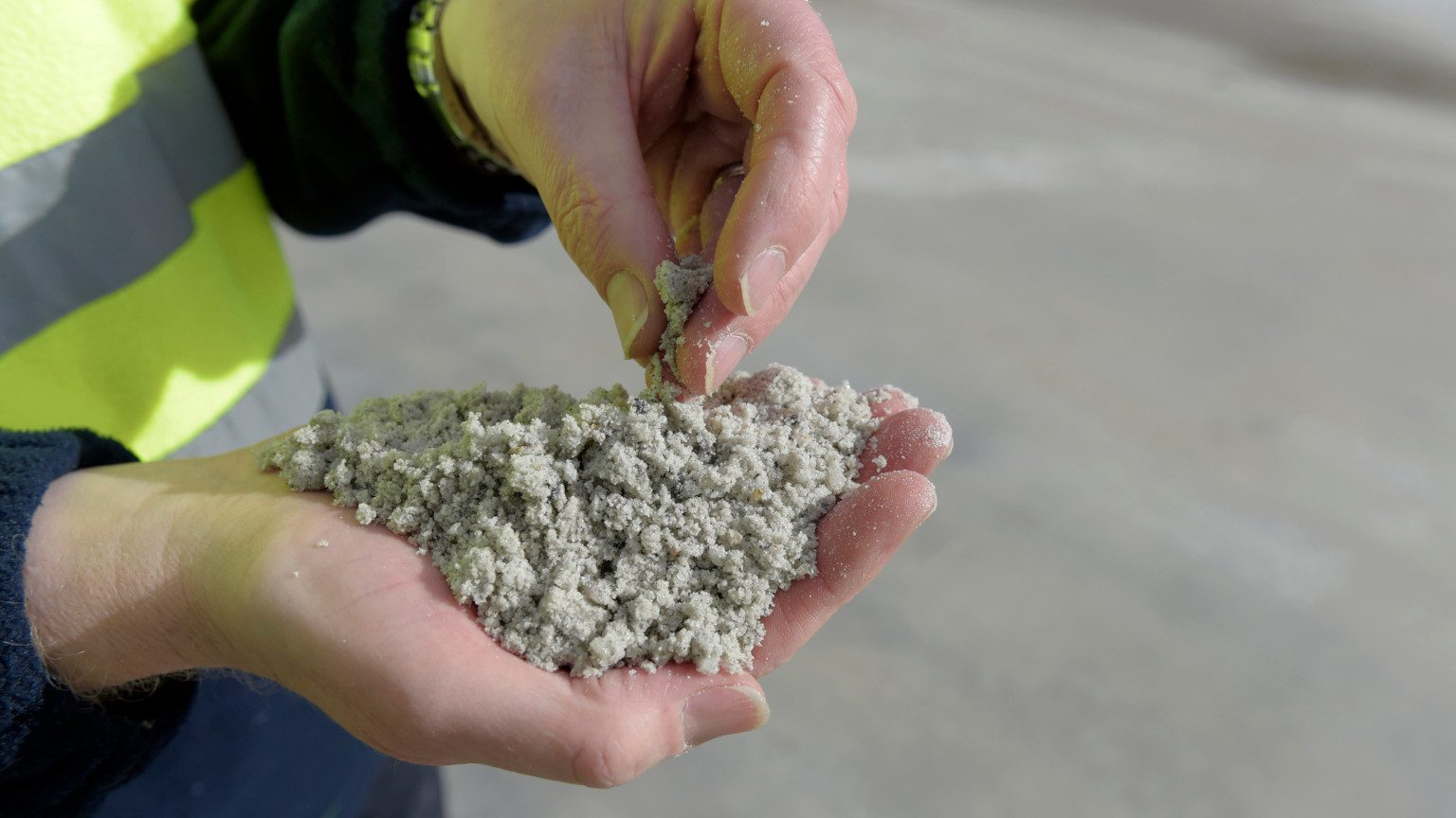 Close up of worker's hands holding processed lithium