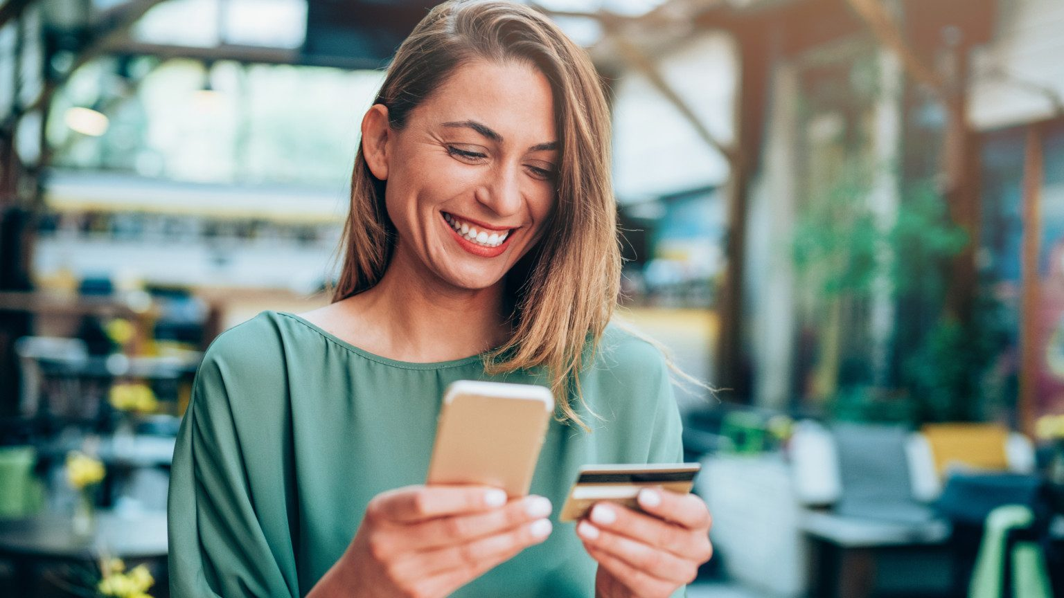 Smiling woman holding her smartphone and a credit card