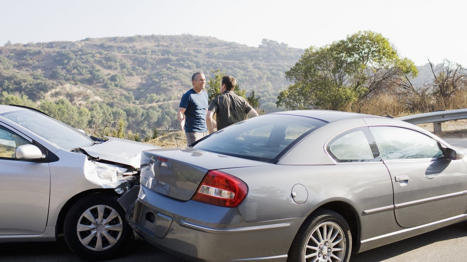 Two Men Arguing At Car Accident Scene On A Hill