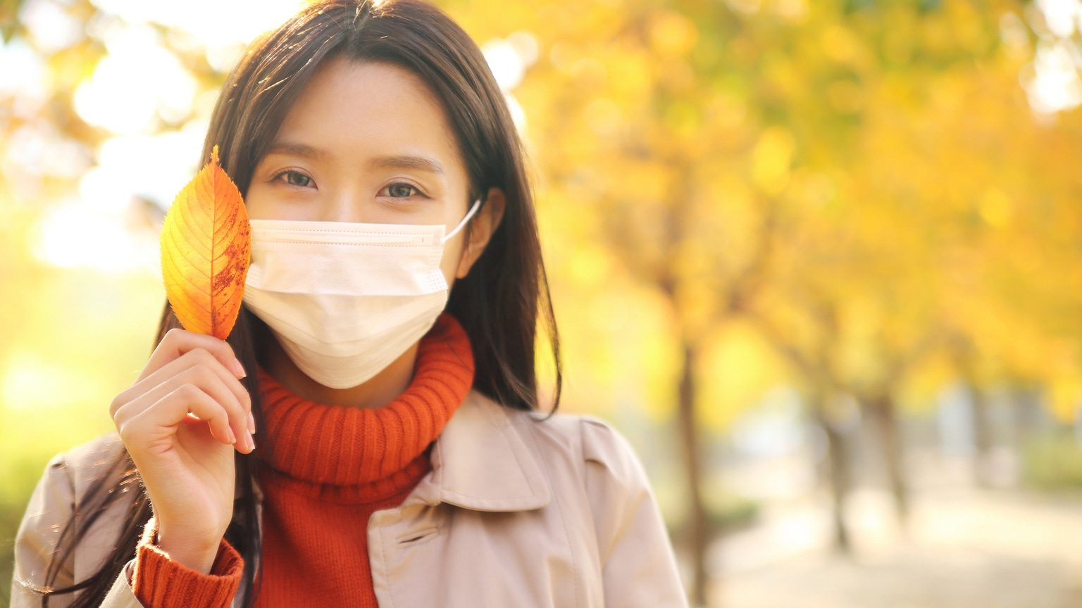 Woman walking outdoors during the fall wearing a face mask