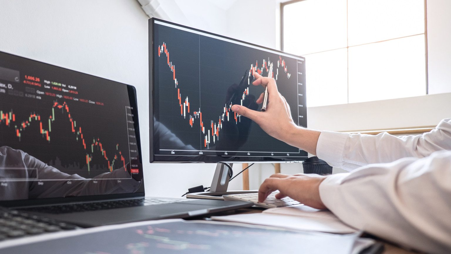 Person's hands analyzing the stock market on two computer screens