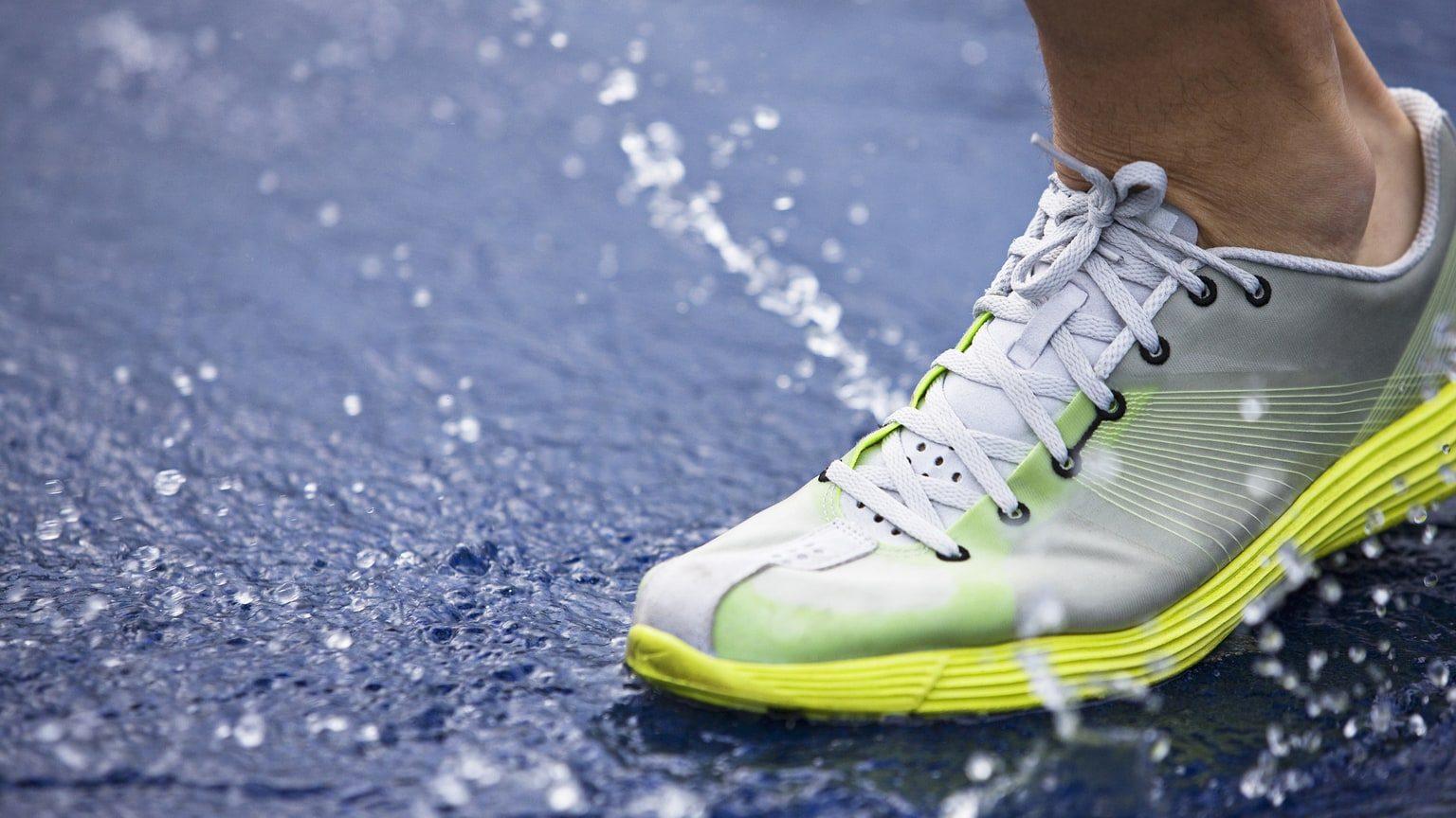 Closeup of grey running shoe on wet pavement