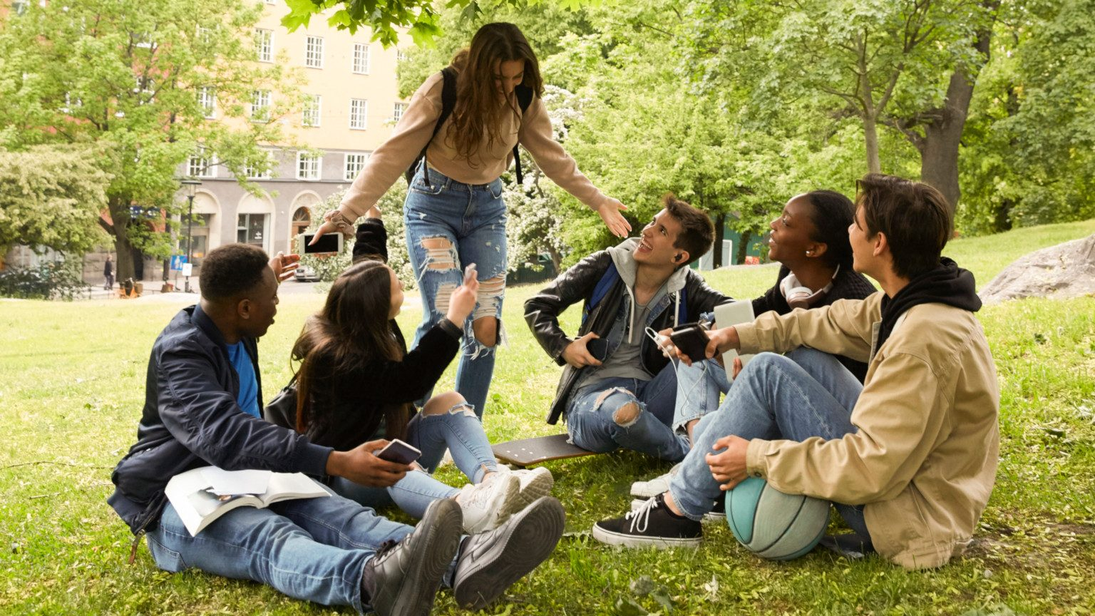 A group of teenagers sitting together outside on grass