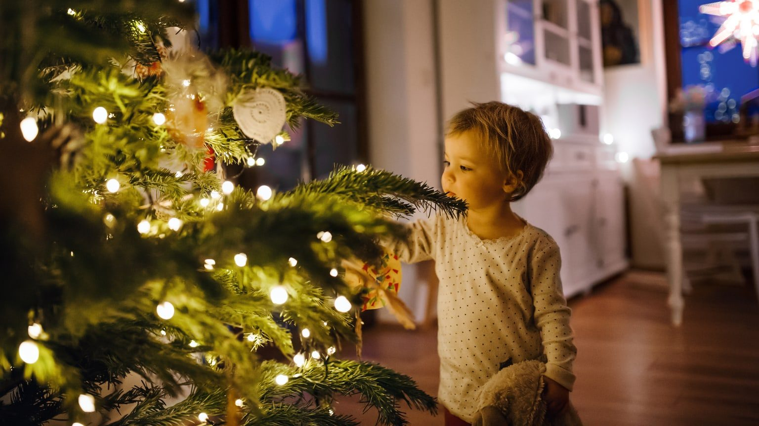 Little girl touching a decorated Christmas tree in her home