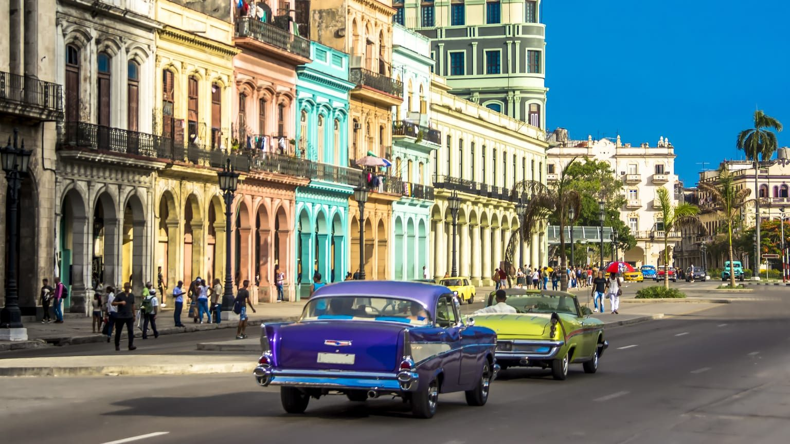 Vintage car driving down a sunny street in Cuba