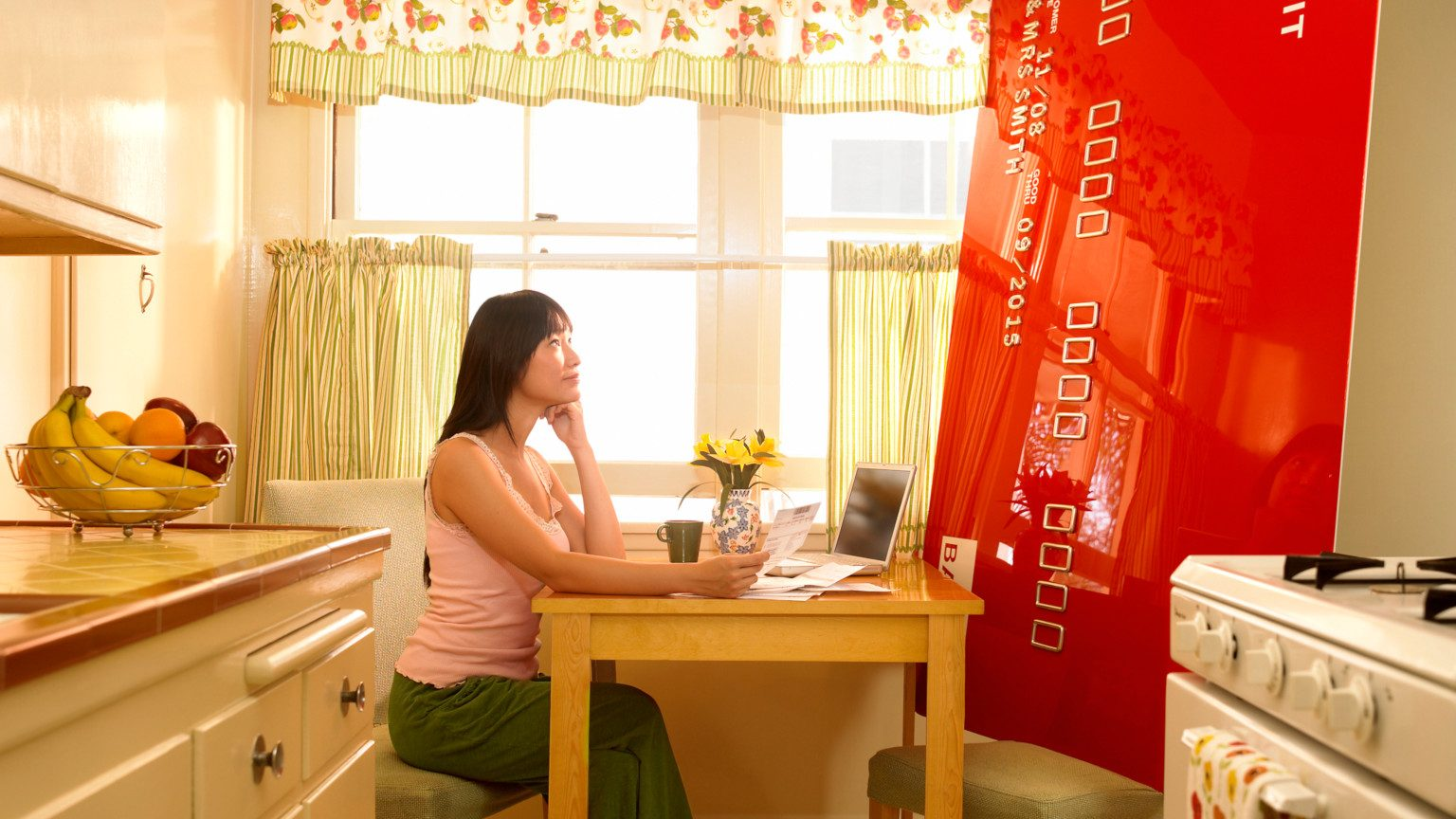 Asian woman sitting in her kitchen looking up at a giant credit card